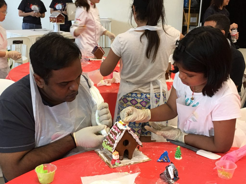 An SMPS father-daughter pair at a cake decorating workshop at The Giving Family Festival