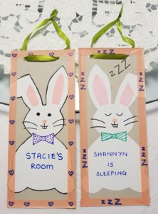 Door hangers made from cardboard packaging and rabbits cut out from a previous craft