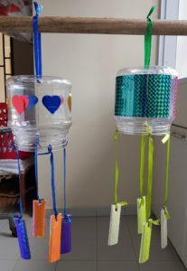 Wind chimes made out of plastic containers and newspaper pellets