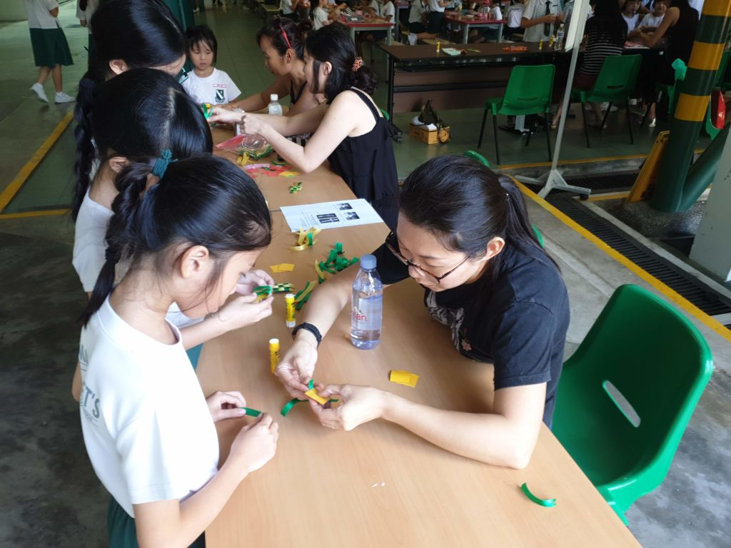 A parent volunteer showing a student how to weave a ketupat